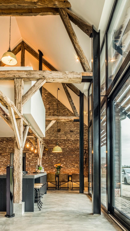 Renovatie woonboerderij met behoud van oude houten spanten, strakke witte kern met woonkeuken en studie en lamellenzonwering boven extra hoge houten puien