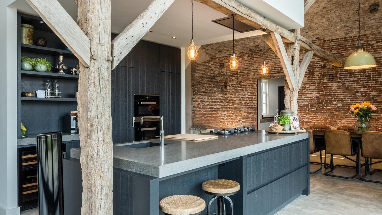 Renovatie woonboerderij Sprundel. Het kookeiland past precies tussen de originele houten spantenstructuur. De houten balken geven extra sfeer in de keuken. Het uitstekende deel van het volume met de studie leunt ook echt op de houten horizontale spantbenen.