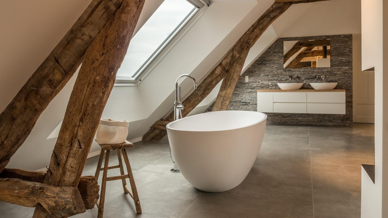 Renovatie woonboerderij Sprundel. Het vrijstaande Corian bad staat precies tussen de 2 oude spanten. Een groot dakraam geeft veel licht op het bad.