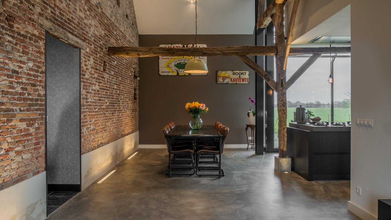 Renovatie woonboerderij Sprundel. Een comfortabele eethoek met grote zwarte tafel en stoelen. Het houten spant is boven de tafel langs verbonden met de oude metselwerk muur.