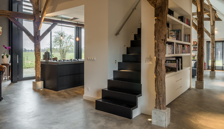 Renovatie woonboerderij Sprundel. Een strakke stalen trap geeft achter de kastenwand van de keuken toegang tot de daarboven gelegen studie.