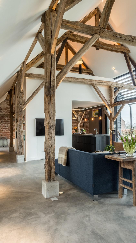 Renovatie woonboerderij Sprundel. Betonnen sokkels beschermen de onderkanten van de houten spanten. Verlichting bij de houten spanten accentueert de structuur van de houten balken.