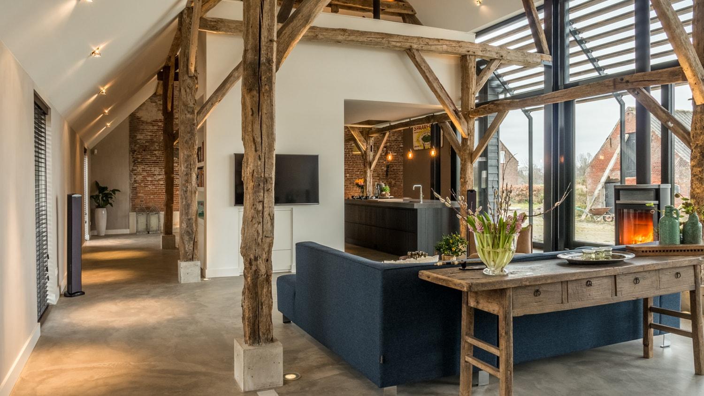 Renovatie woonboerderij Sprundel. Een comfortabele hoekbank met zicht op de woonkeuken-en-studie met daarachter de eetkamer.