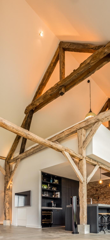 Renovatie woonboerderij Sprundel. Het plafond van de woonkamer, en ook de houten spanten, zijn bijna 8m hoog en gevel veel sfeer aan de boerderij.