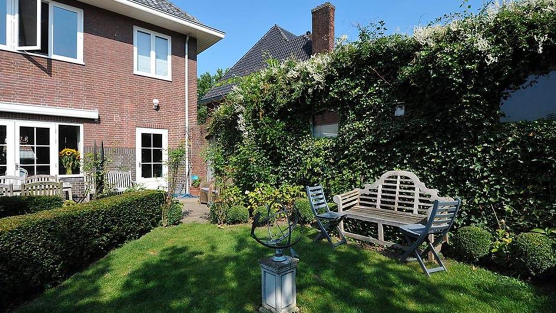 Verbouwing woonhuis met grote woonkeuken. De bestaande tuin met klimop begroeide schuur/garage. De deur beneden maakt plaats voor een grote wanddoorbraak.