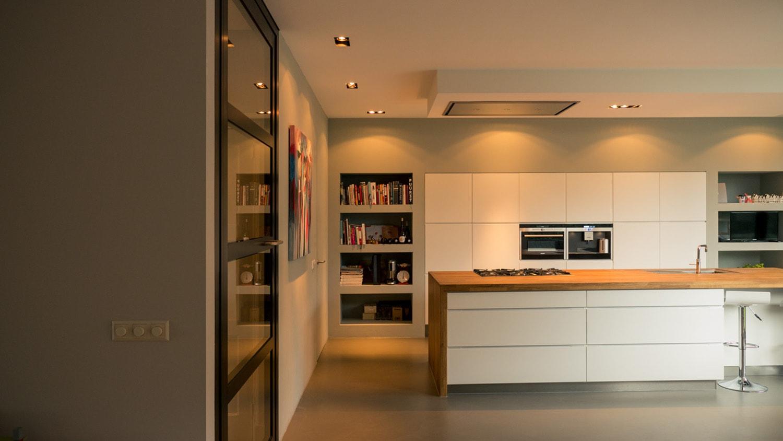 Verbouwing woonhuis met grote woonkeuken. Naast de kastenwand zitten diepe nissen voor kookboeken en apparatuur. De vlakken geven textuur en sfeer aan de verder strakke ruimte.