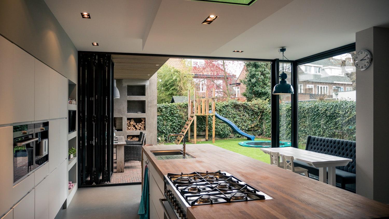 Verbouwing woonhuis met grote woonkeuken. Zicht op de tuin en veranda met de vouwschuifpui helemaal geopend.