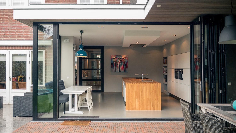 Verbouwing woonhuis met grote woonkeuken. Zicht vanuit veranda op woonkeuken.