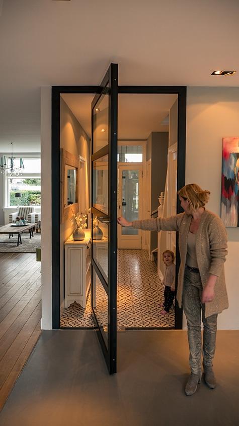 Verbouwing woonhuis met grote woonkeuken. Aluminium pivotdeur tussen entree en keuken.