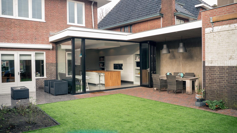 Verbouwing woonhuis met grote woonkeuken. De aluminium vouwschuifpui in volledig geopende stand. Directe doorloop richting veranda en tuin.