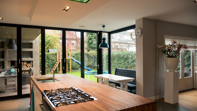 Verbouwing woonhuis met grote woonkeuken. De grote aluminium vouwschuifpui geeft uitzicht op de veranda en de tuin.