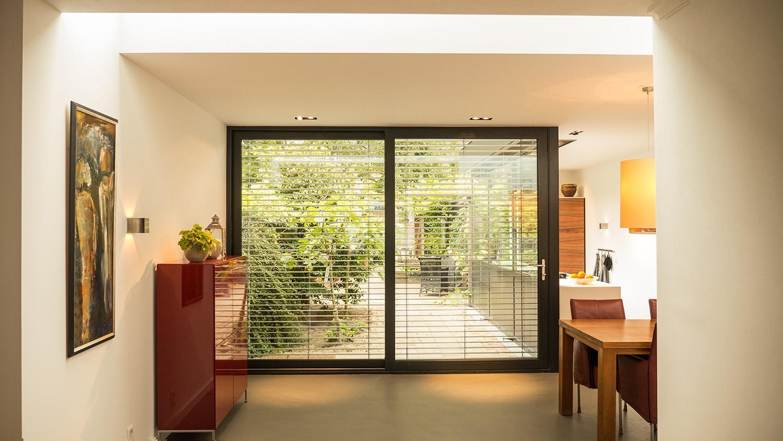 Aanbouw met moderne keuken. De lamellen zijn in 2 delen bedienbaar. 1 voor het vaste glas van de pui en 1 voor de schuifdeur zelf. Anders kan je in de zomer niet naar buiten als de lamellen naar beneden staan.