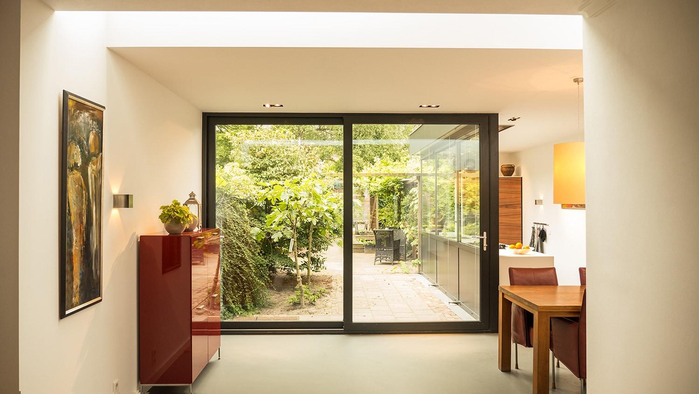 Aanbouw met moderne keuken. De lichtstraat geeft extra licht in de bestaande woonkamer. De aluminium schuifpui geeft toegang tot een hele diepe tuin.