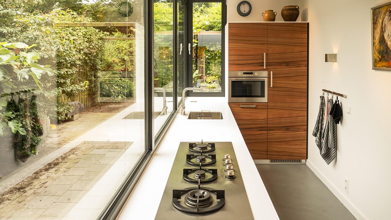 Luxe smalle aanbouw met keuken pal op het zuiden, aluminium schuifpui en lamellen zonwering