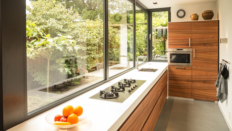 Aanbouw met moderne keuken. Himacs keukenblad met houtiger kastjes en kastenwand. De vlier is een gietvloer. Het smalle kozijn naast de hoge kast geeft extra uitzicht op de tuin.