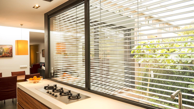 Aanbouw met moderne keuken. De lamellen kunnen in horizontale stand als de zon te fel is. Zo hou je de warmte buiten en het licht binnen.