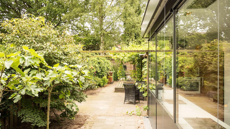 Aanbouw met moderne keuken. Het glas in de pui van de smalle aanbouw reflecteert de tuin en valt nu minder op.