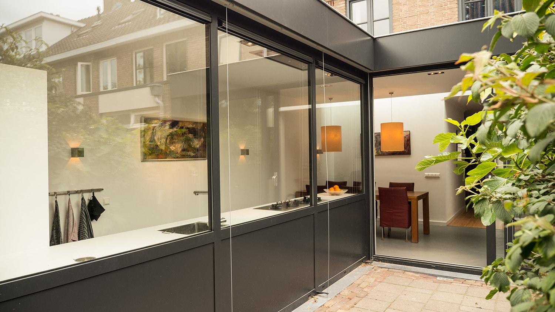 Aanbouw met moderne keuken. De horizontale aluminium lamellen zijn volledig omhoog en vallen weg in de dakrand. De lichtstraat op de achterwand knipt de woning visueel in 2 delen: de aanbouw en de bestaande woonkamer. Het verschil in vloerafwerking benadrukt dit.