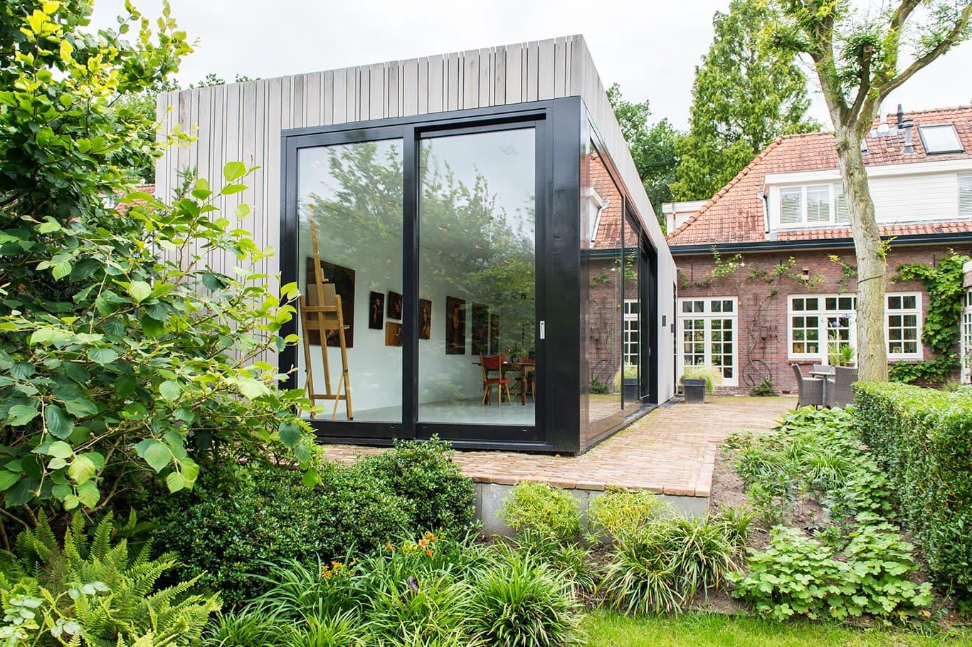 Atelier voor portretschilder in Breda. De overgang tussen aanbouw met atelier en de bestaande woning is bewust contrasterend gehouden. Dus een volledig andere stijl geeft duidelijk aan dat het om een toevoeging gaat aan een bestaand gebouw en valt af te lezen als een bijna autonoom gebouw, maar toch onderdeel van het geheel.