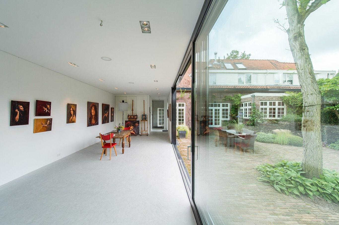 Atelier voor portretschilder in Breda. Contrast tussen het strakke interieur van het atelier en het traditionele exterieur van de woning.