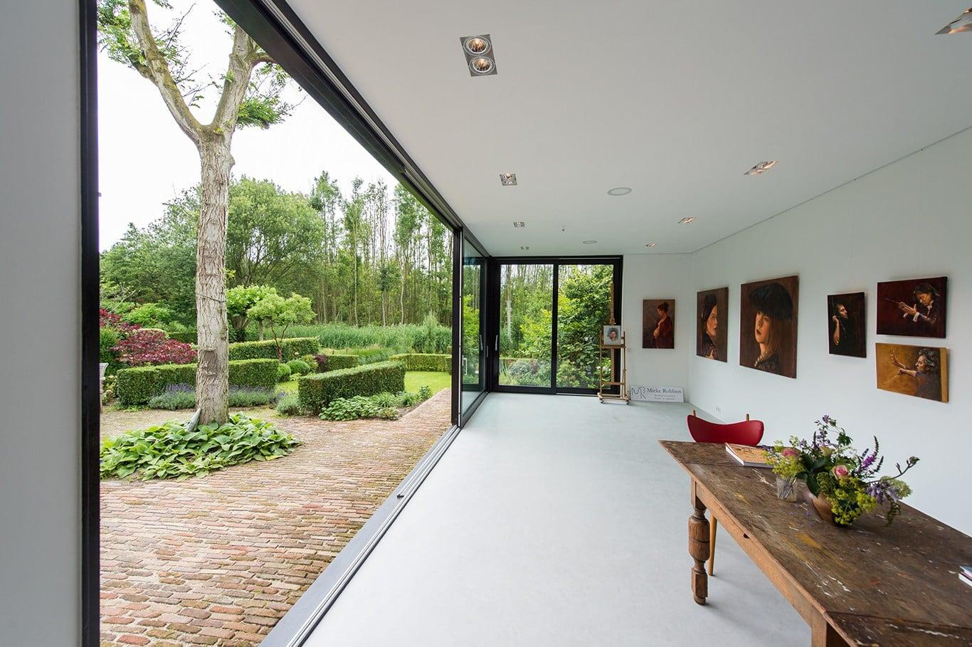 Atelier voor portretschilder in Breda. De glazen schuifpuien zijn nu volledig geopend en geven prachtig zicht op de tuin en het terras ernaast. Het atelier is op het noorden gericht en heeft geen directe zoninval.