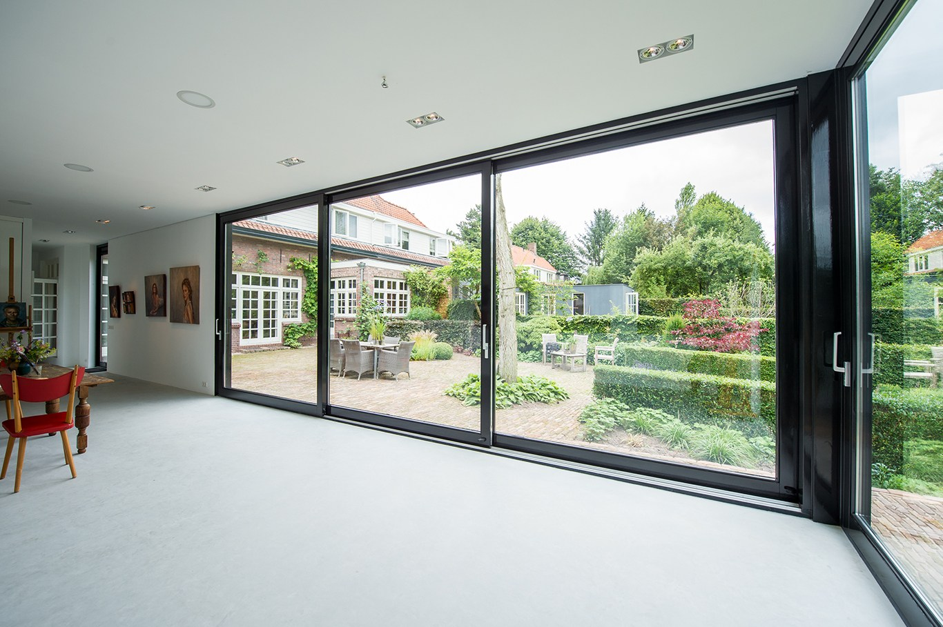 Atelier voor portretschilder in Breda. De grote glazen schuifpuien geven zicht op de bestaande woning en en de tuin.