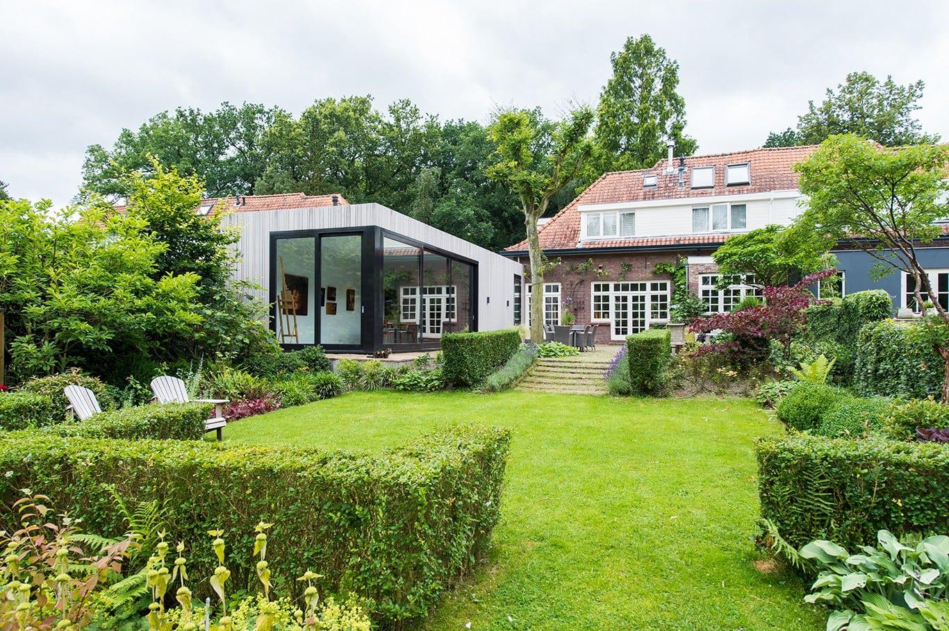 Atelier voor portretschilder in Breda. Zicht vanuit achterin de tuin op de langwerpige aanbouw met atelier. Doordat het atelier hoger ligt dan het achterste deel van de tuin geeft dit extra uitzicht op de tuin en creëert dit extra lucht en licht in het atelier.