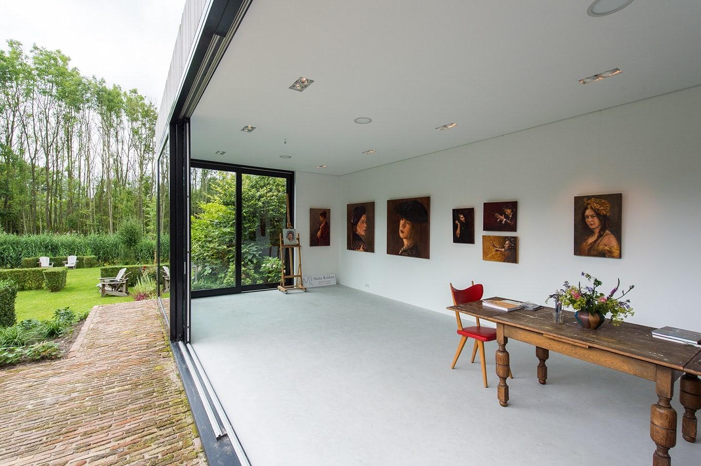 Atelier voor portretschilder in Breda. Rondom het gehele atelier kun je schilderijen ophangen aan een rails in het plafond. Mieke heeft zo maximale indeelbaarheid op de muren.