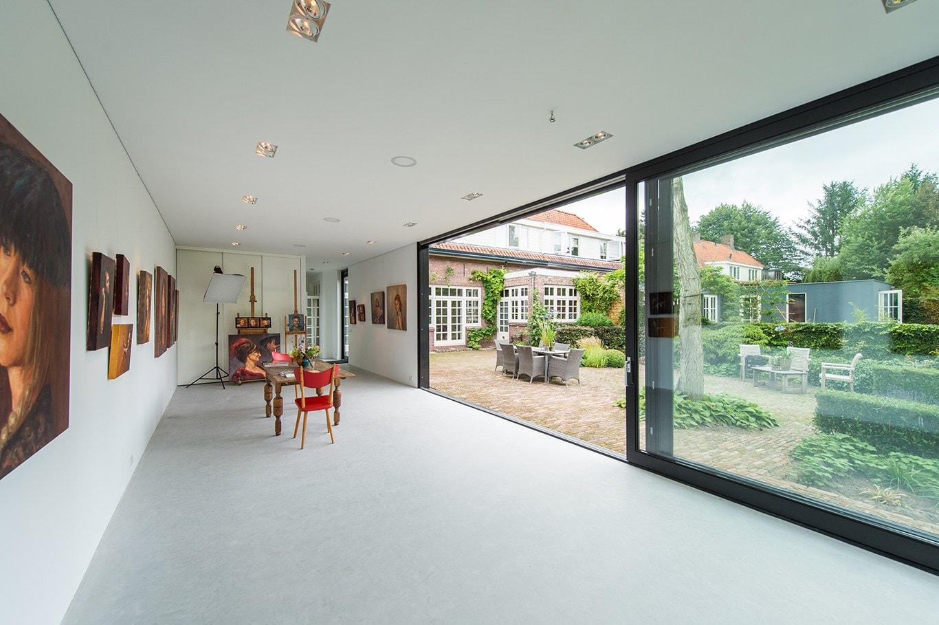 Atelier voor portretschilder in Breda. De brede glazen schuifpuien geven mooi uitzicht op de tuin mar ook op de bestaande woning.
