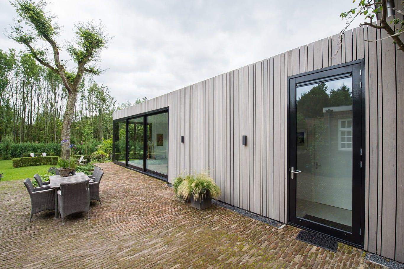 Atelier voor portretschilder in Breda. Vanuit de woning kijk je door de grote glazen deuren richting tuin achter het atelier. Dit geeft meer lucht en breedte aan de tuin die nu overblijft direct achter de woning en naast het atelier. Dit was anders te massief geworden.