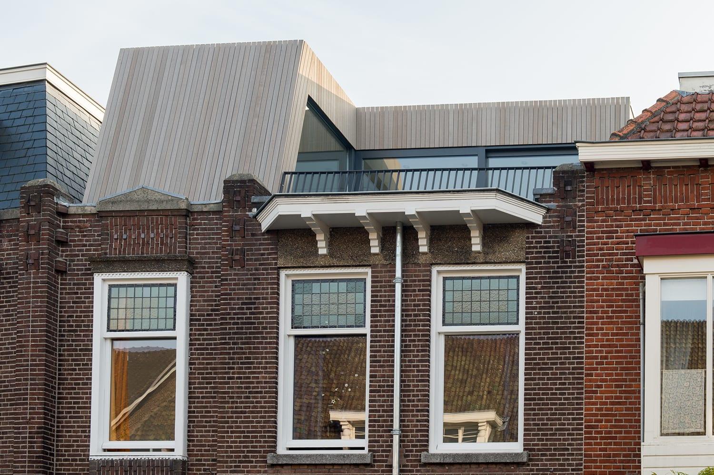 Dakopbouw woning in westen red cedar. Dakopbouw woning aan voorzijde met houten gevelbekleding, dakterras en glazen schuifpui. Het hout contrasteert sterk met de bestaande metselwerk gevelstenen.