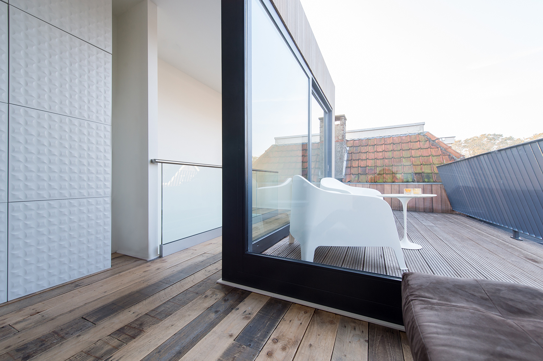 Dakopbouw woning in westen red cedar. Zicht vanuit de studieplek op het dakterras. Er komt zowel in de overloop als de studieplek veel licht binnen door toepassing van de glazen schuifpui met vast glas.