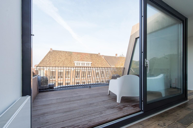 Dakopbouw woning in westen red cedar. De brede glazen schuifpui geeft toegang tot het mooie dakterras aan de voorzijde.