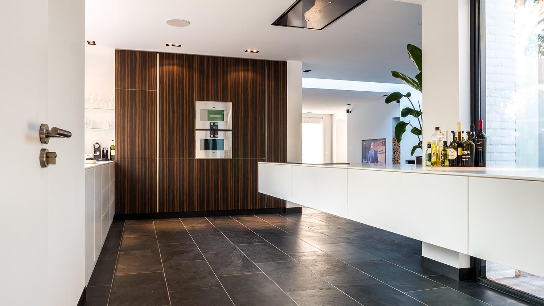Luxe renovatie met zwevende dakopbouw, maatwerk keuken met zwevend HI-MACS keukenblok en houtfineer kastenwand