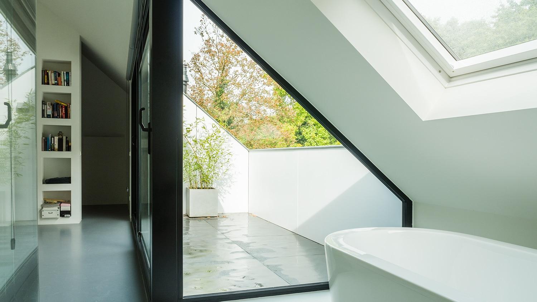 Verbouwing en renovatie zolder met loggia. Een in het dakvlak liggende loggia geeft licht en ruimte in de zolder. Zo kun je buiten staan op de zolder. Het geeft ook prachtig zicht op de bomen.