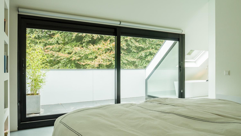Verbouwing en renovatie zolder met loggia. Prachtig zicht vanuit bed op aluminium schuifpui, loggia en omringend bos. Heerlijk wakker worden.