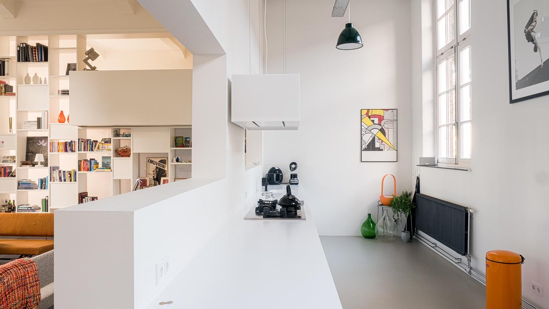 Verbouwing woning in school. De lichte witte keuken versus de kast als leefwand in de woonkamer.