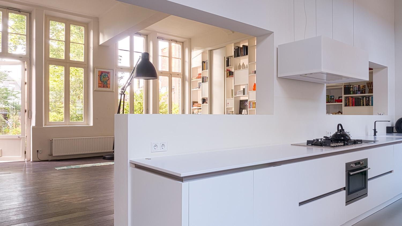 Verbouwing woning in school. De keuken valt onder de opening. Je hebt perfect uitzicht op de woonkamer maar andersom wordt de keuken verborgen door de hogere openingen.