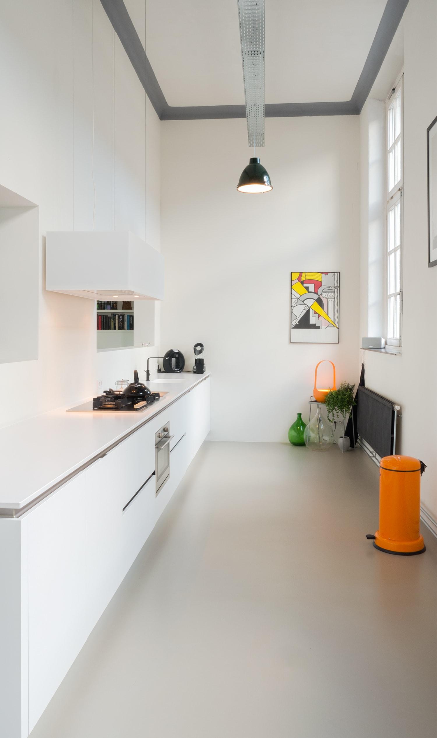 Verbouwing woning in school. Langwerpige witte keuken in oude gang van school. Perfecte plek voor de keuken door de smallere breedte. De hoogte van 4.5m geeft veel lucht aan deze ruimte. De kozijnen rechts zijn noord georiënteerd en geven d perfecte lichtinval.