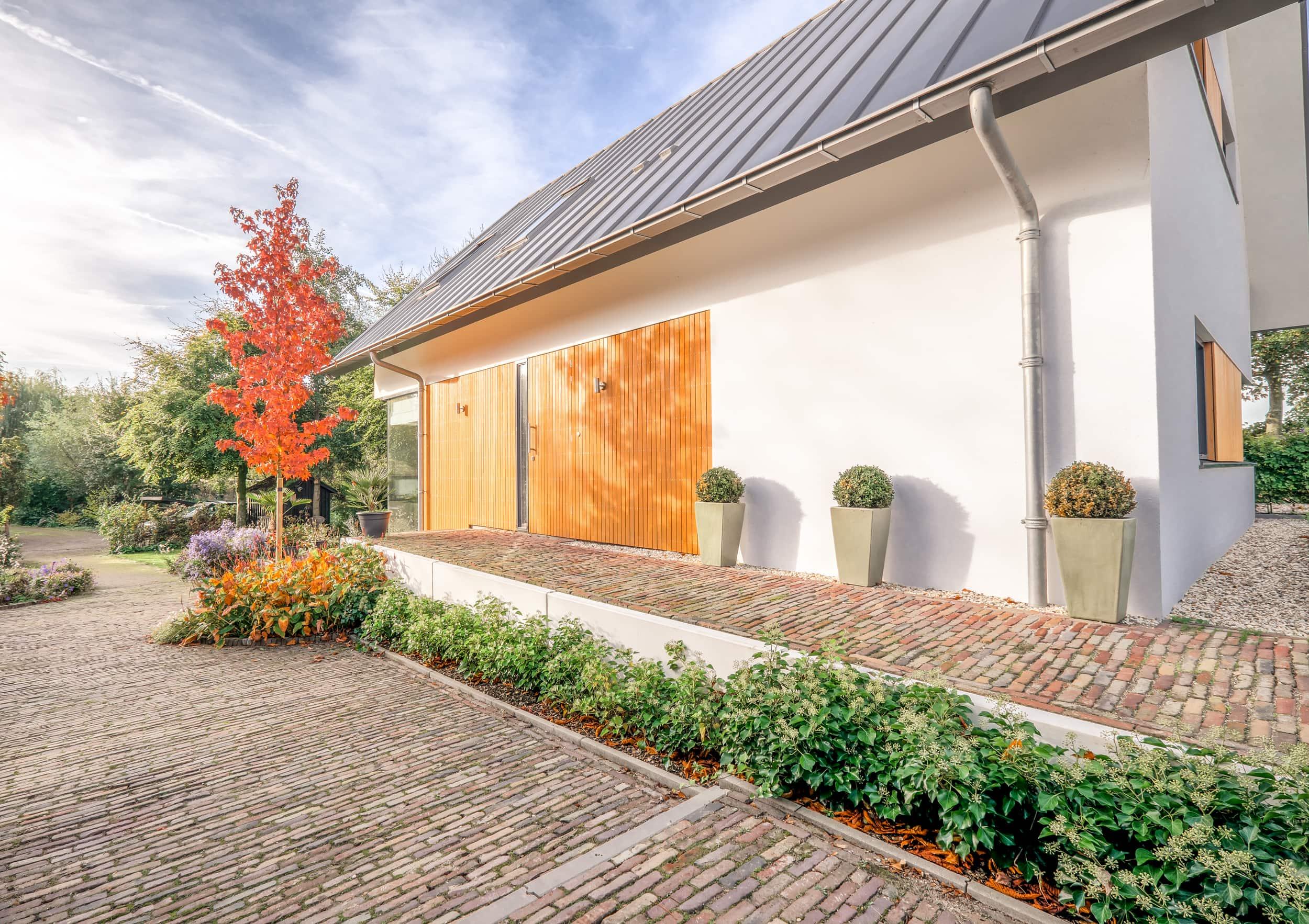van-os-architecten-nieuwbouw-dijkwoning-rottekade-zevenhuizen-gevel-met-stalen-dak-houten-gevebekleding-en-stucwerk