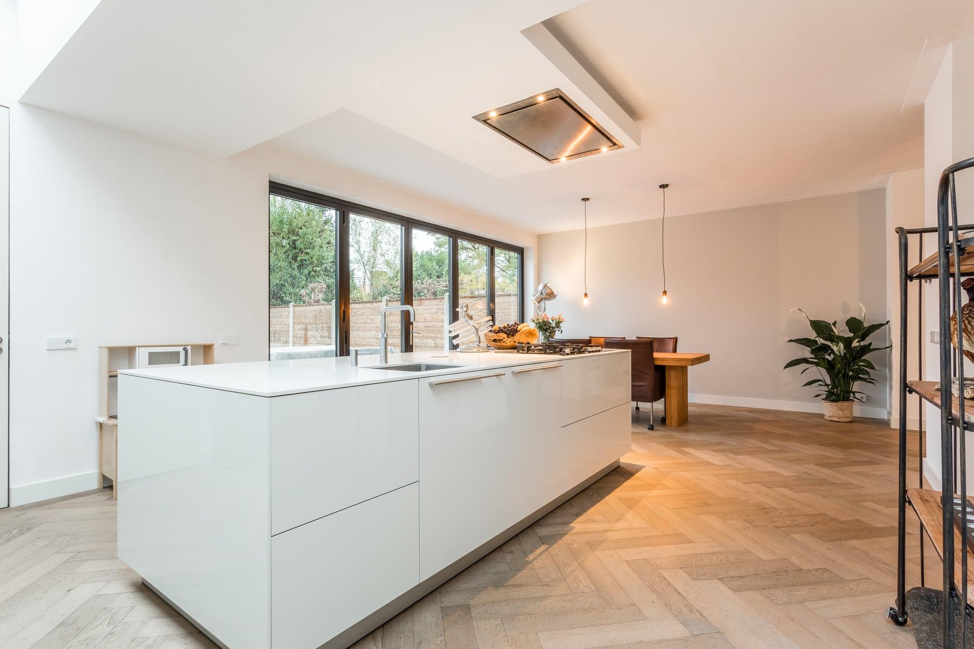 van-Os-architecten-verbouwing-2-onder-1-kapper-Valkenierslaan-Breda-strakke-himacs-kookeiland-en-luxe-houten-visgraat-parketvloer