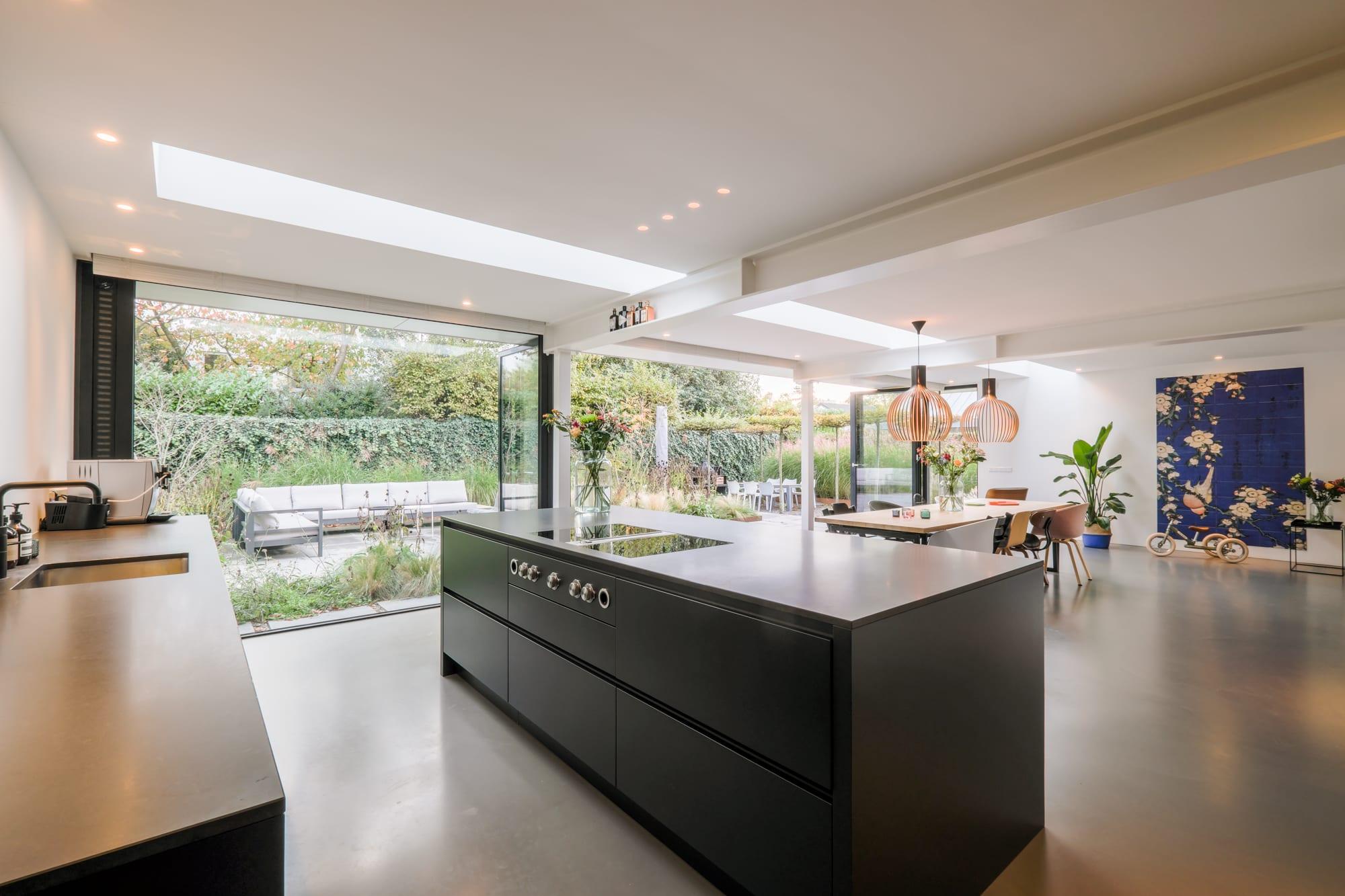 van-os-architecten-breda-ontwerp-moderne-aanbouw-met-aluminium-vouwschuifpui-kookeiland en zicht-op-de-tuin