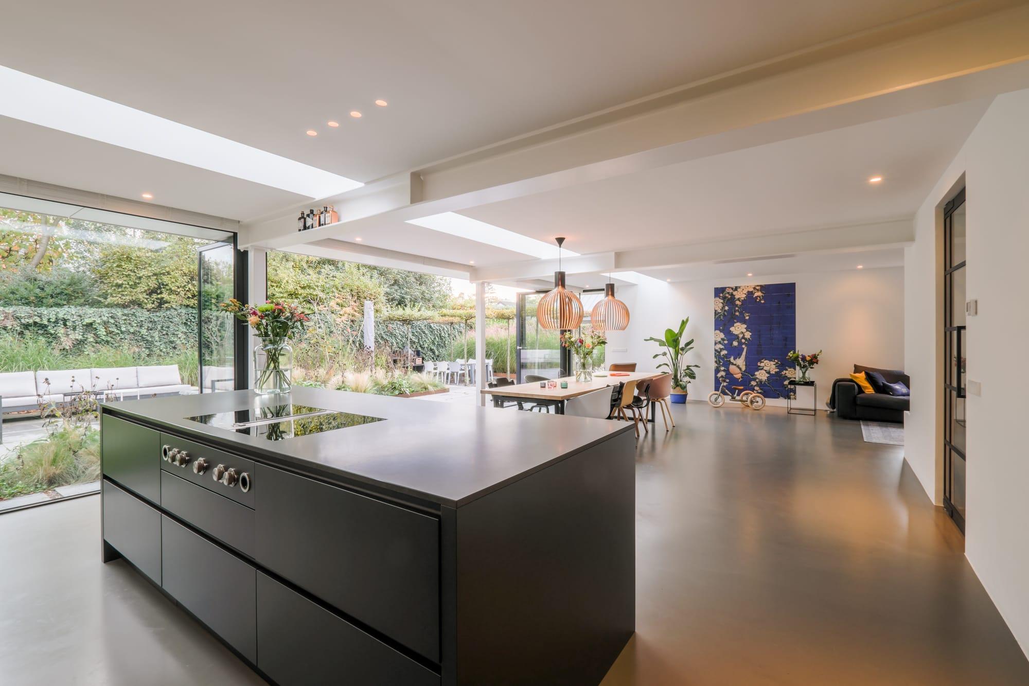 van-os-architecten-breda-ontwerp-moderne-aanbouw-met-aluminium-vouwschuifpui-kookeiland-en-zicht-op-eettafel-en-woonkamer