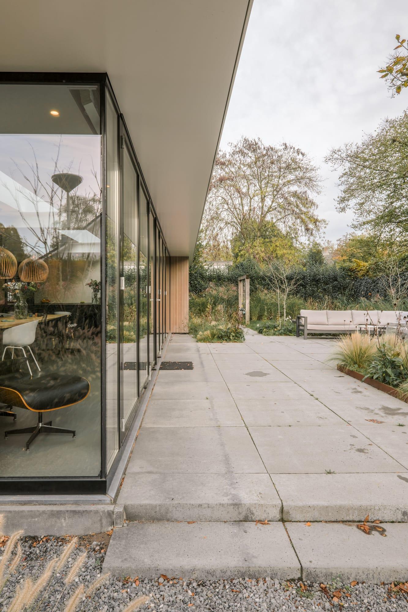 van-os-architecten-breda-ontwerp-moderne-aanbouw-met-aluminium-vouwschuifpui-overstek-op-zuidgevel