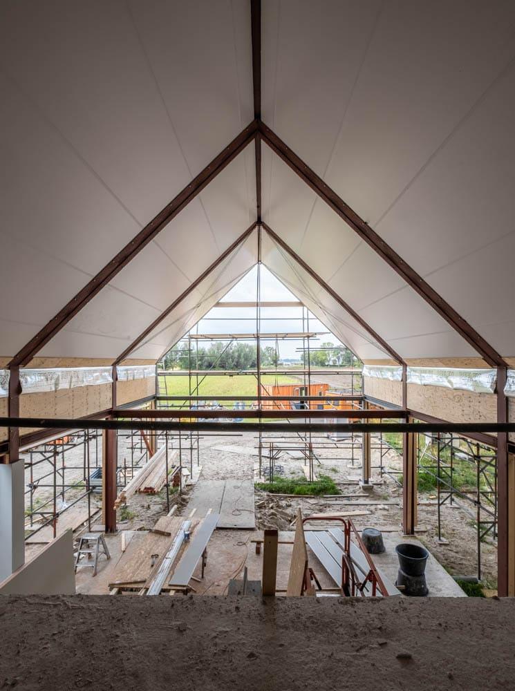 van-os-architecten-breda-ontwerp-moderne-schuurwoning-oosteind-in-rieten-dakbedekking-en-padoek-gevelbekleding-met-aluminium-puien-zicht-vanuit-vide-op-weiland