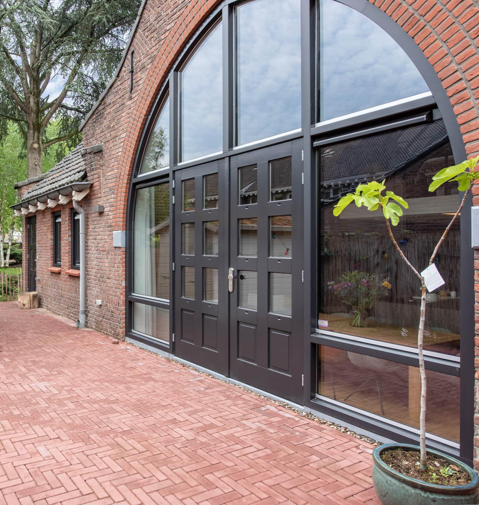 van-os-architecten-verbouwing-kapel-tot-woonhuis-oranjeboomstraat-breda-hoge-pui-richting-tuin-vanuit-woonkamer-en-keuken