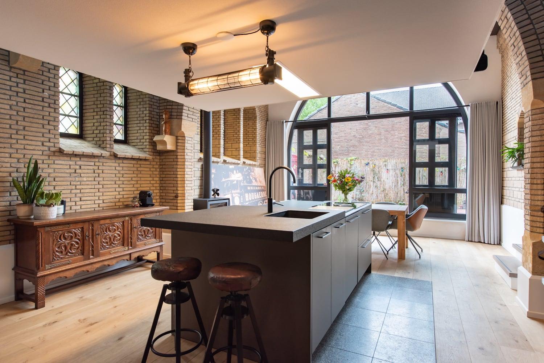 van-os-architecten-verbouwing-kapel-tot-woonhuis-oranjeboomstraat-breda-kookeiland-onder-verdiepingsvloer-met-zicht-op-tuin