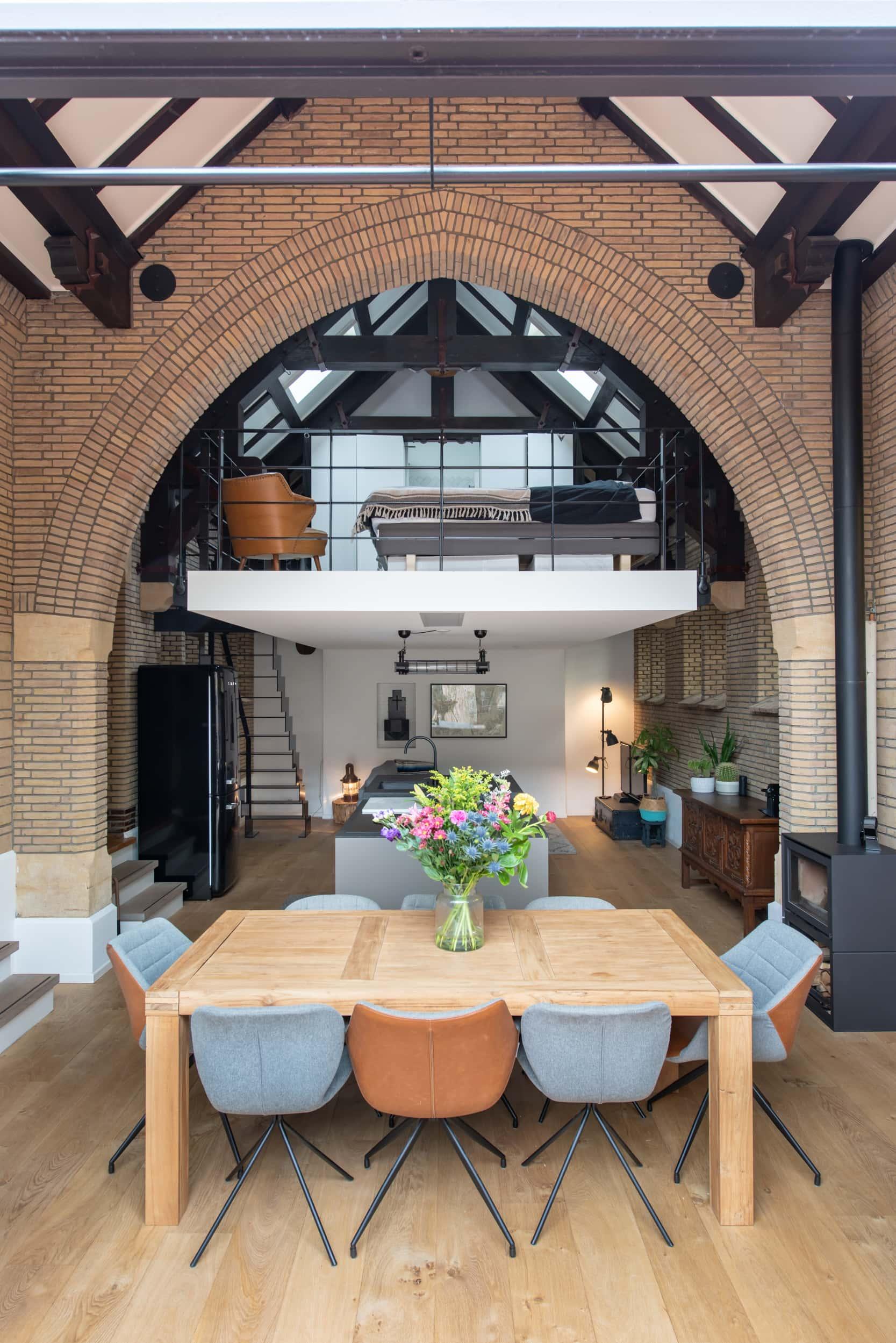 Verbouwing kapel tot woonhuis in Breda met een nieuwe verdiepingsvloer met slaapkamer boven een woonkamer met woonkeuken en gebruik van alle originele elementen