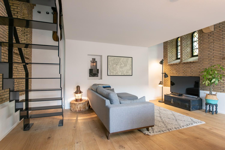 van-os-architecten-verbouwing-kapel-tot-woonhuis-oranjeboomstraat-breda-woonkamer-met-stalen-trap-naar-verdieping-met-slaapkamer